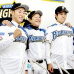 巨人からトレードで移籍し、栗山監督(中央)とポーズをとる日本ハムの矢野(左)と須永=11日、札幌ドーム