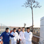 「奇跡の一本松」を背に伊藤コーチ(左端)の説明を聞く(右から)早大の小太刀、山城、小島、長谷川